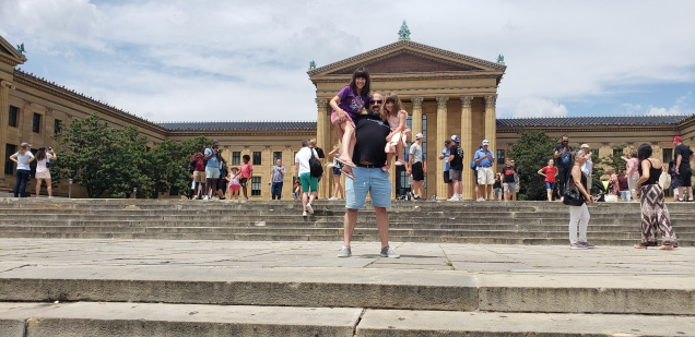 Jake making the classic Rocky pose, on the Rock steps with Reagan and Rebecca perched up on each arm