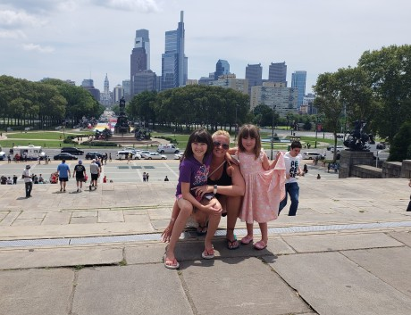 Beth Holding Reagan and Rebecca while crouching on the Rocky steps with Philadelphia in the Background.